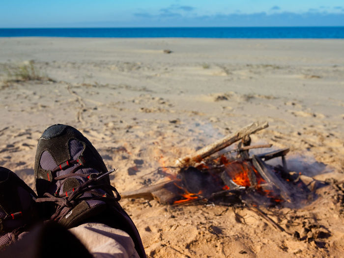 Low section of person sitting by campfire at beach