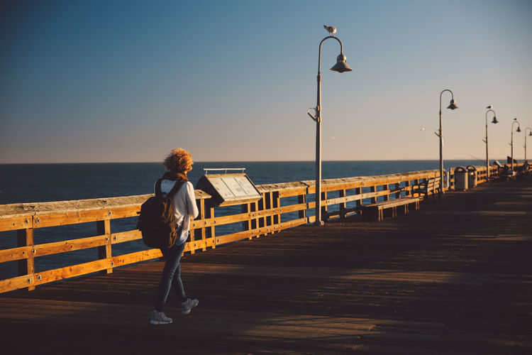 Full length of mid adult woman walking on pier over sea during sunset