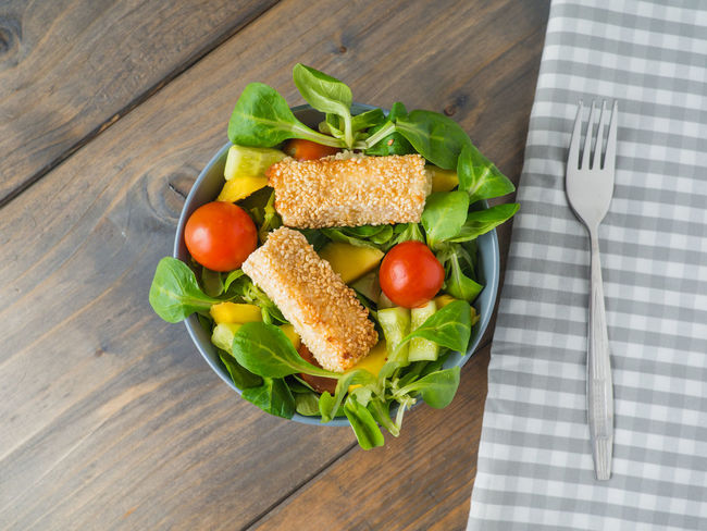 High angle view of baked feta cheese with salad on a wooden background Baked Cheese! Diet Feta Feta Cheese Food Fresh Salad  Freshness From Above  Fruit Green Healthy Eating Healthy Food Indoors  Leaf Lettuce Salad Mango Meal Mixed Salad Salad Bowl Snack Tomato Tomatoes Vitamins