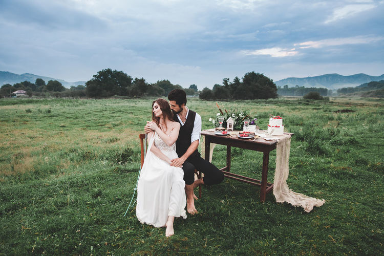 Full Length Of Wedding Couple Sitting On Chair At Farm Against Cloudy Sky
