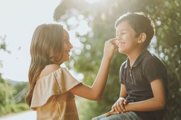 Smiling sister touching nose of brother outdoors