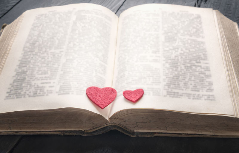 Two red hearts on the pages of an old open book, displayed on a vintage black table. A concept for the love of education, a romantic novel or a love story. Romance Romantic Valentine Book Education Heart Shape Knowledge Literature Love Lovers Day No People Open Open Book  Page Red Heart Still Life