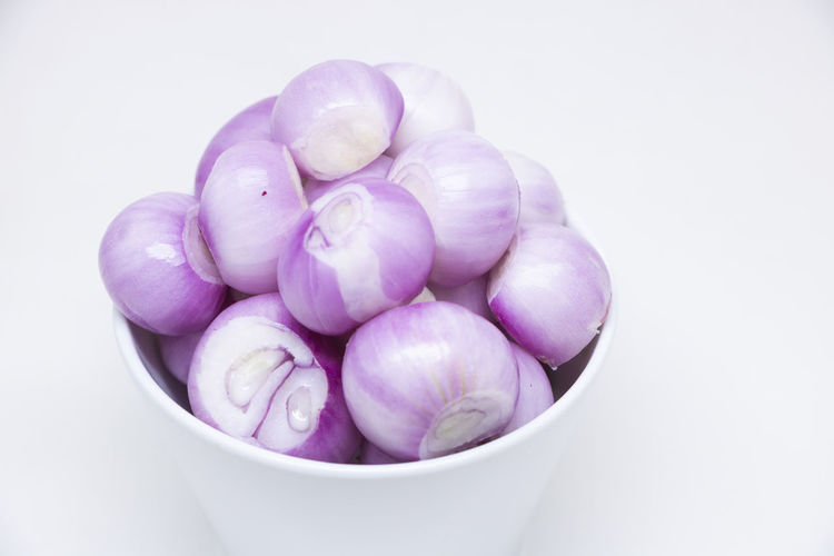 High angle view of grapes in bowl against white background