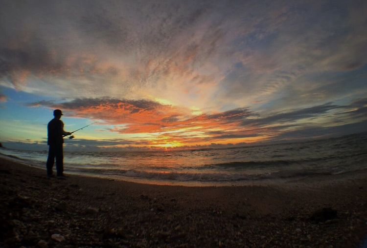 Work is for people who can't fish... 😌👻 Standing Sea Sunset Cloud - Sky Sky Outdoors Nature Beauty In Nature Traveling Home For The Holidays Beach Enjoying The Sun Silhouette Vscocam Candid Photography