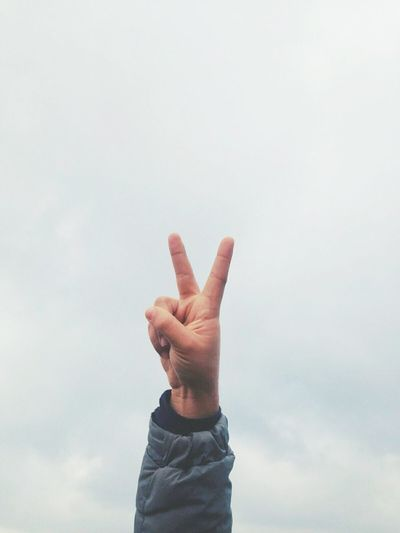 Cropped Image Of Hand Making Peace Sign Against Cloudy Sky