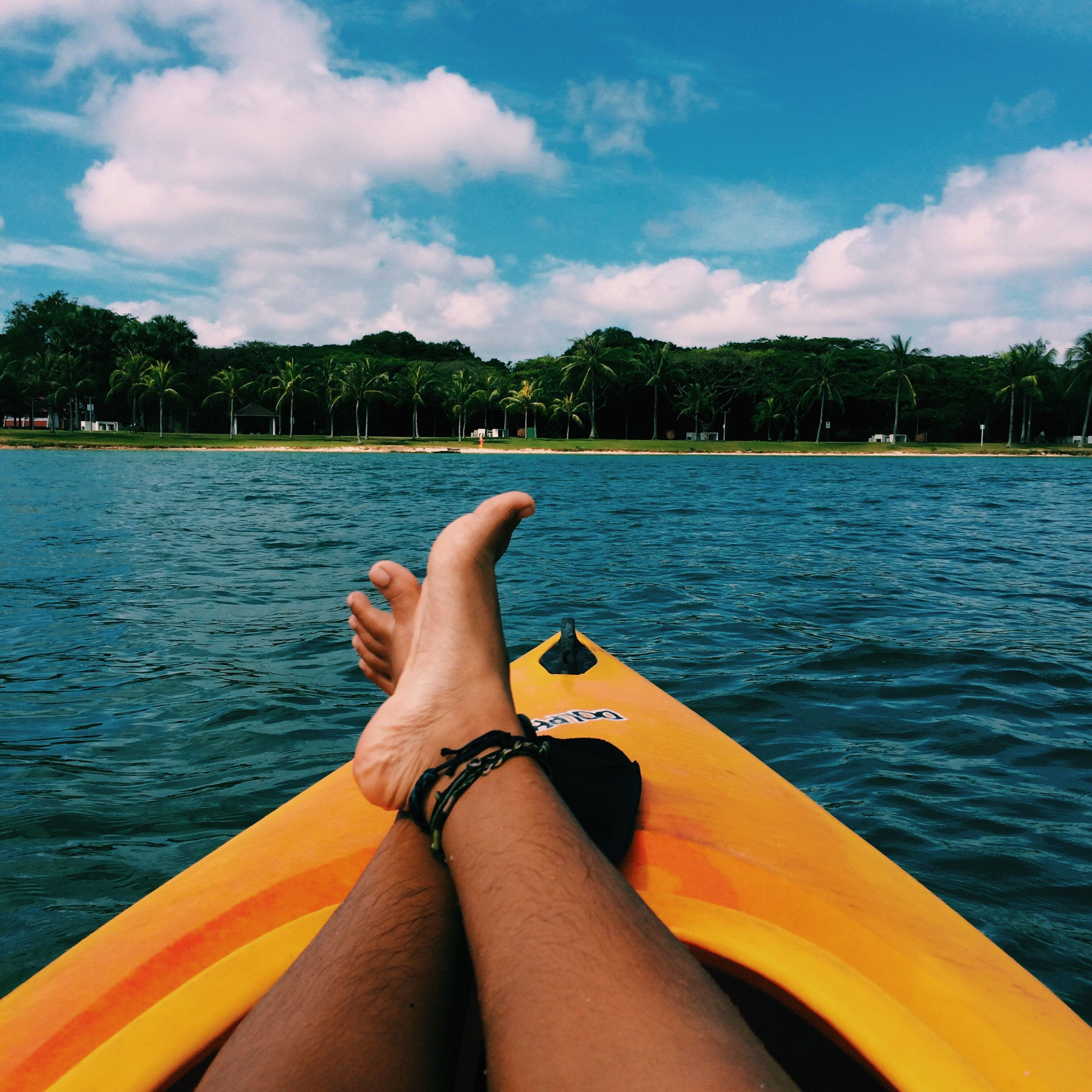 low section, relaxation, person, personal perspective, young adult, water, sky, tourism, lake, sensuality, leisure, tree, legs crossed at ankle, vacations, lying down, leisure activity, tourist, young women, resting, relaxing, weekend activities, blue, tranquility, cloud, tranquil scene, day, outdoors