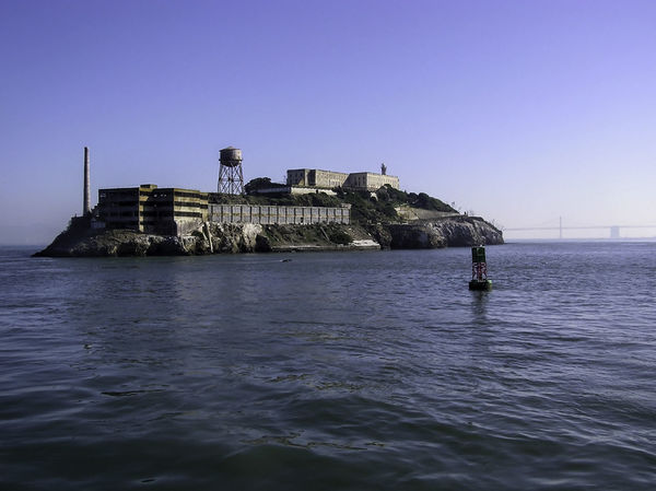The waters surrounding Alcatraz (showing why it was difficult to escape) and a view of the Rock; background is a view of the Bay Bridge in a fading view. We were leaving the place (which is the centerpice of an action thriller called The Rock). Alcatraz was an island prison, with very few escapees from the island, but was finally shut down and is now a tourist attraction. Alcatraz Alcatraz In Sight Alcatraz Island Architecture Blue Building Exterior Built Structure Clear Sky Day No People Outdoors Sea Tranquility Water