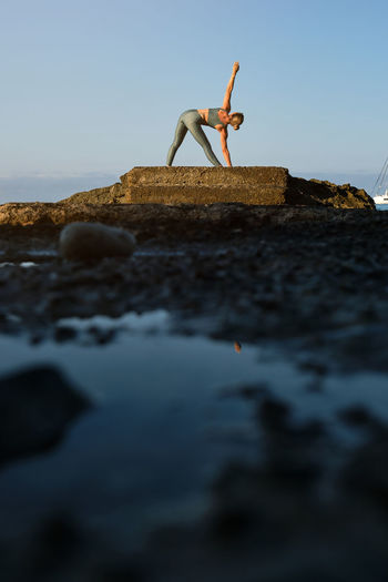 Low angle view of man on rock at beach against clear sky