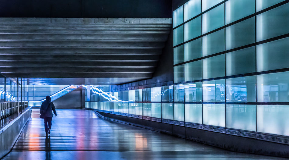 Man Walking On Elevated Walkway By Illuminated Building In City