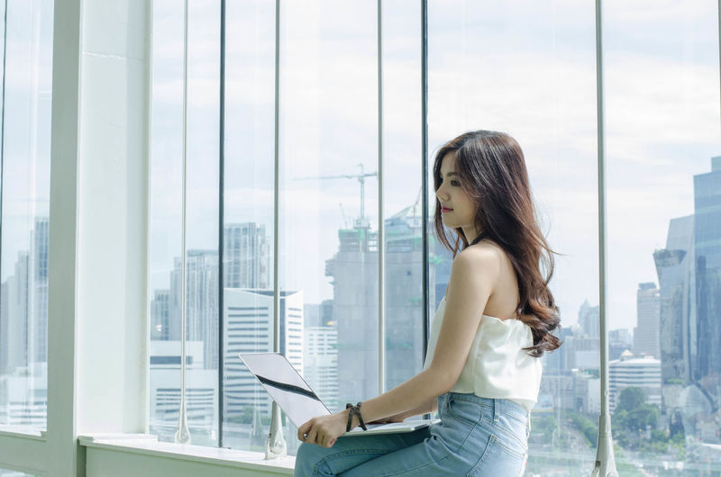 Young business woman hand holding laptop computer selective focus working woman in office concept City Copy Space Woman Adult Architecture Building Building Exterior Built Structure Business Businesswoman City Cityscape Corporate Business Glass - Material Laptop Lifestyles Looking Office Office Building Exterior Side View Using Laptop Window Wireless Technology Women Young Adult