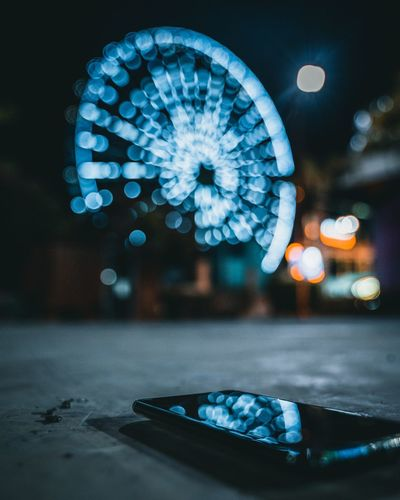 Close-up of illuminated ferris wheel at night