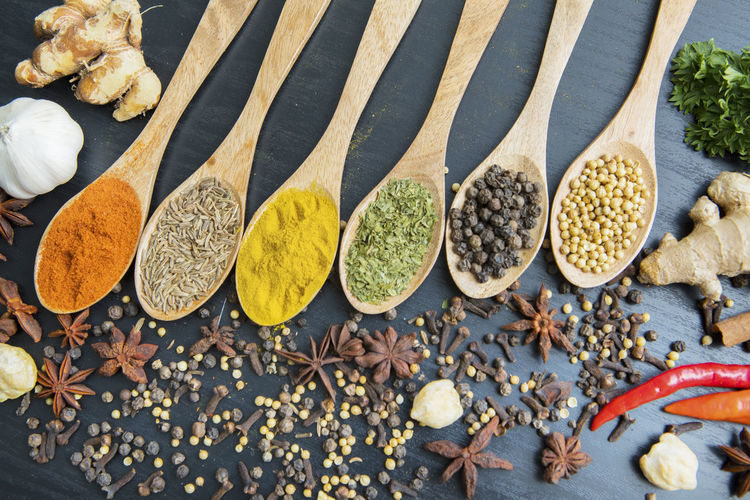 High angle view of spices in wooden spoon and table