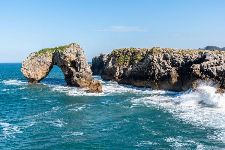 Rocks in sea against blue sky