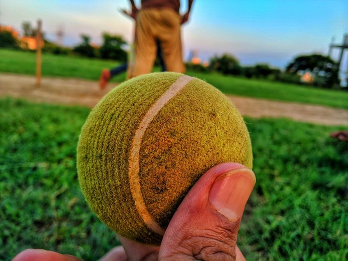 Close-up of hand holding ball over grass