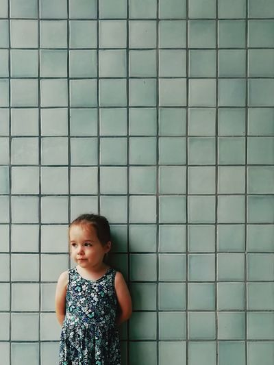 Cute girl standing against wall