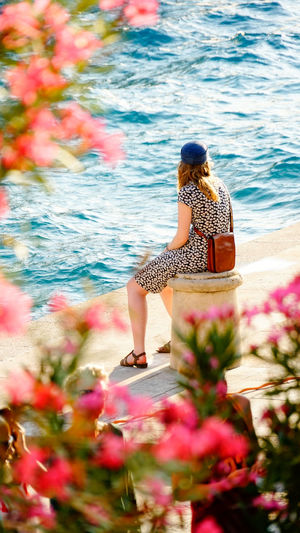 Woman at the harbour Adult Adults Only Beauty Croatia Day Fair Day  Flower Full Length Harbor Korčula Multi Colored Nature One Person One Woman Only One Young Woman Only Only Women Outdoors People Rear View Sitting Vacations Water Young Adult Young Women