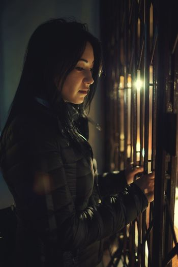 Side view of young woman standing by illuminated lamp at night