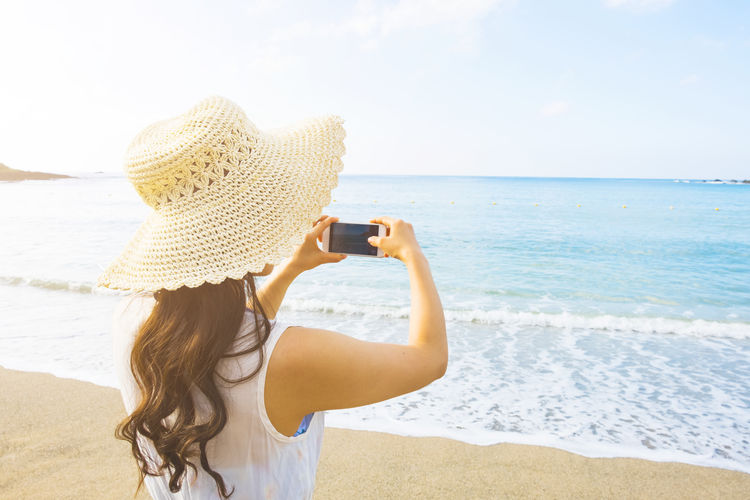 Rear View Of Woman Photographing From Mobile Phone At Beach