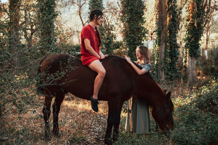 Woman sitting on horse with friend standing in forest