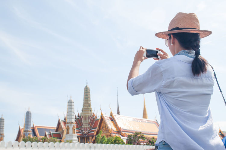 Woman using mobile phones to take photo of tourist destinations in Thailand. Traveling concept, travel, tourist, map, holiday, summer, woman, lifestyle, vacation, adventure, outdoor, asian, landmark, activity, traveling, map sing, freedom, smart phone, technology, using mobile, using, city Using Phone Using Summer Holiday Photography Themes Technology Photographing Architecture Sky Built Structure Wireless Technology Real People Religion Lifestyles One Person Belief Spirituality Building Exterior Mobile Phone Nature Place Of Worship Camera - Photographic Equipment Leisure Activity Traveling Historic Ancient Pagoda Visiting Stupa Temple