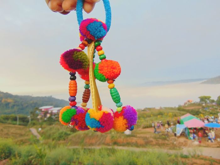Close-up of multi colored balloons hanging on field against sky