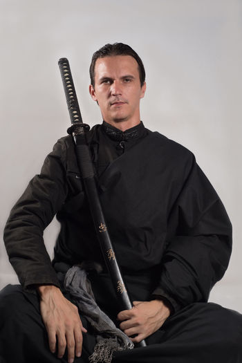 Portrait Of Serious Samurai With Katana Sitting Against Gray Background