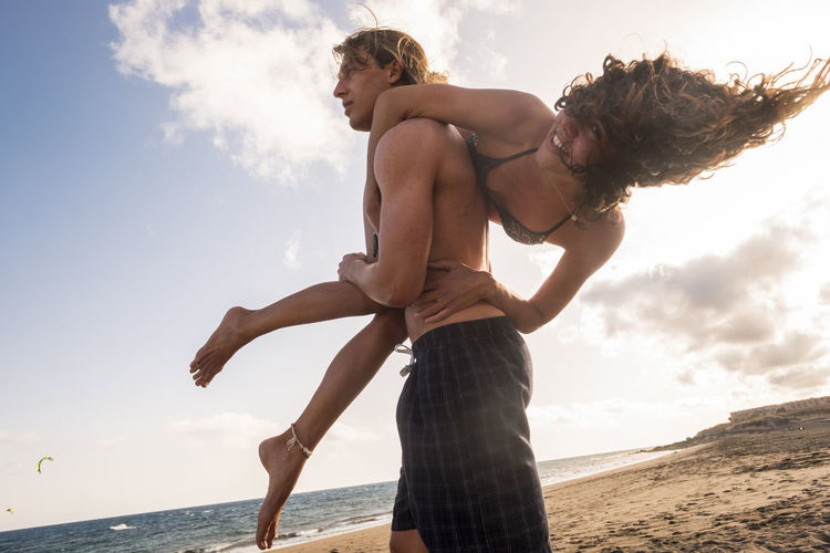 Man carrying woman over shoulder at the beach against sky