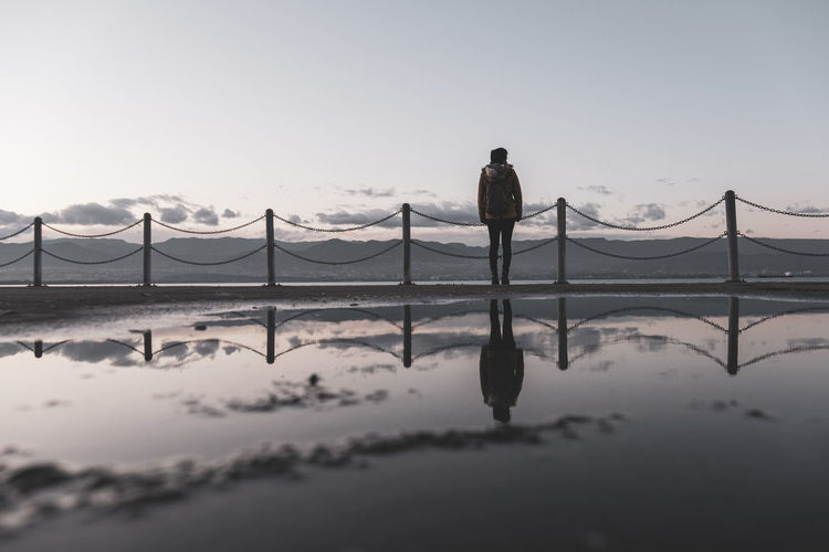 Rear view of silhouette man standing on bridge against sky