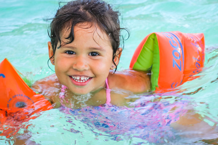 portrait of a happy little girl in a swimming pool wearing floaties Childhood Child Water Pool Swimming Pool Portrait Leisure Activity Smiling Happiness Looking At Camera One Person Front View Headshot Real People Emotion Lifestyles Swimwear Enjoyment Innocence Inflatable  Floating On Water Outdoors Toddler  Girls Diversion