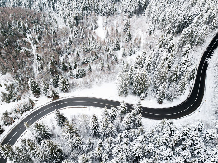 Aerial view of a road winding through snow covered forest