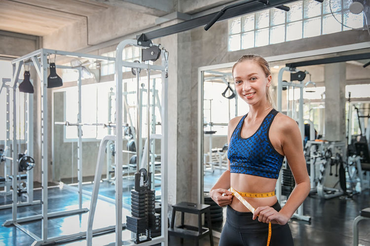 Portrait of smiling young woman measuring waist while standing in gym