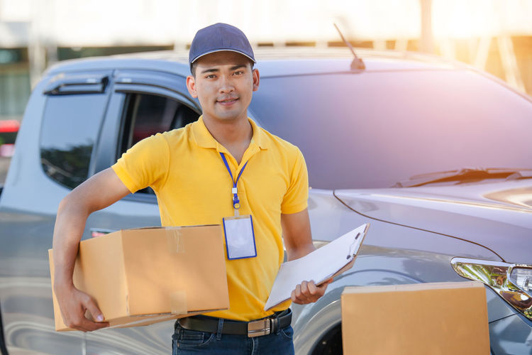 Portrait of smiling delivery person with box standing against car