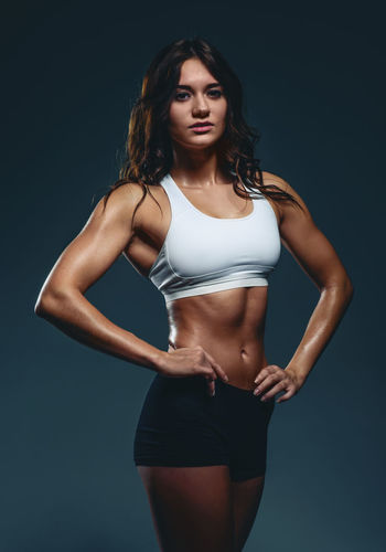 Young beautiful athletic woman, studio shot Athlete Athletic Bodybuilding Figure Looking At Camera Attractive Beauty Biceps Brunette Fitness Fitness Model Muscles Muscular Build One Person Physique  Pose Sport Sportive Standing Strength Strong Studio Shot Women Young Adult Young Women