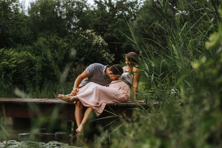 Husband kisses his wife's belly while relaxing at the lake Kiss Love Pregnant Woman Relationship Relaxing Bonding Couple - Relationship Full Length Kissing Lake Leisure Activity Lifestyles Nature Outdoors People Plant Positive Emotion Pregnancy Pregnant Real People Sitting Together Togetherness Two People Water