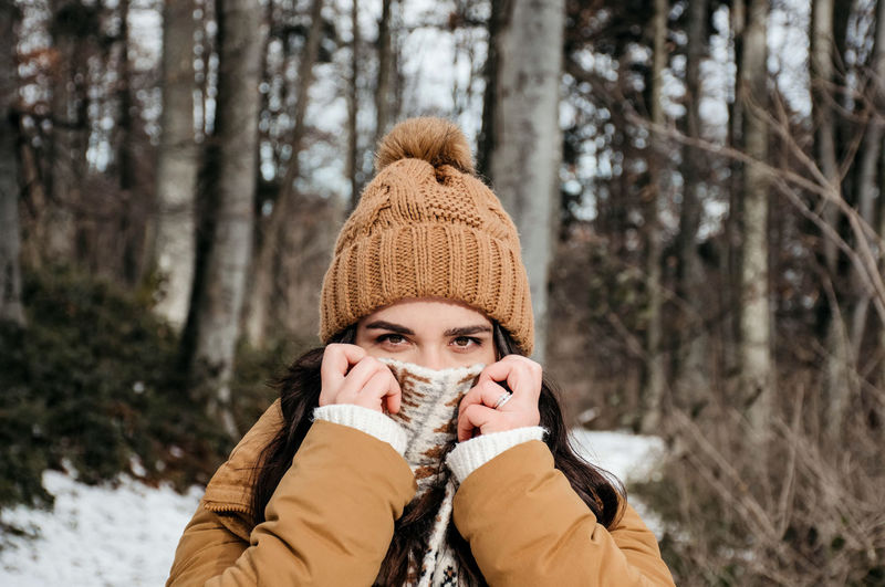 Portrait of young woman holding scarf over her face. winter, outdoors, warm clothes.