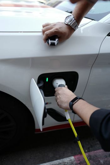 Cropped hand charging electric car