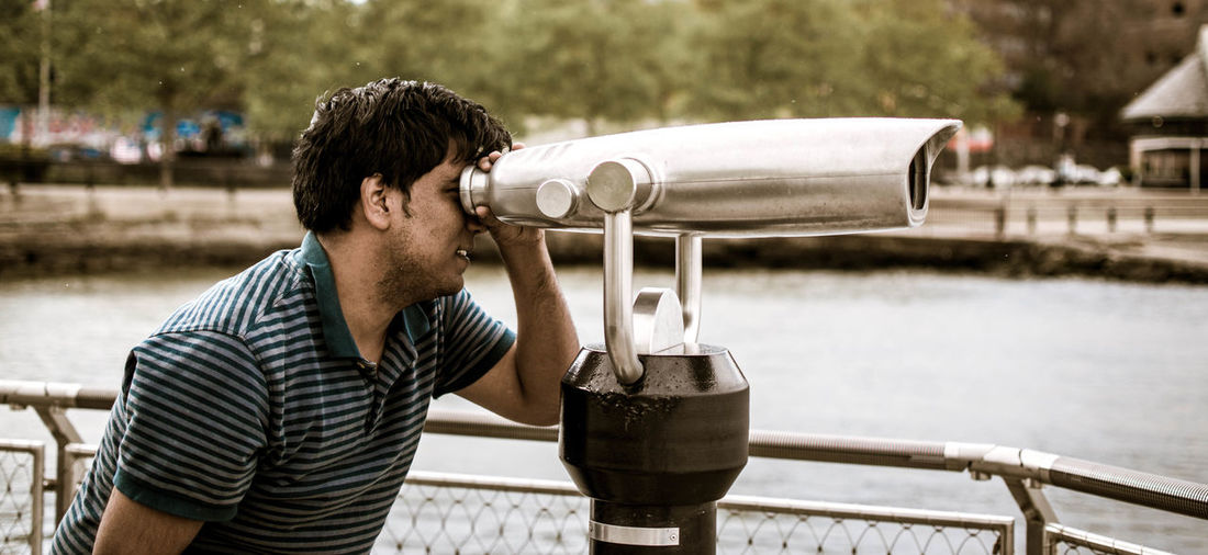 Man looking through binoculars at observation point