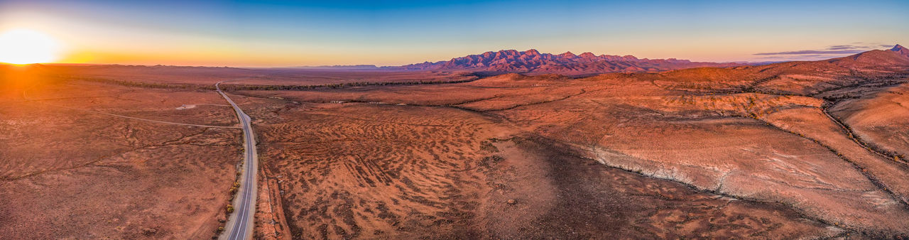 Panoramic view of arid landscape against sky during sunset