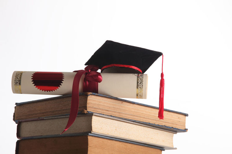 Close-up of diploma and mortarboard on stacked books against white background