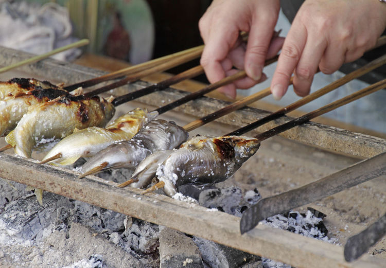 High angle view of person preparing food on barbecue grill