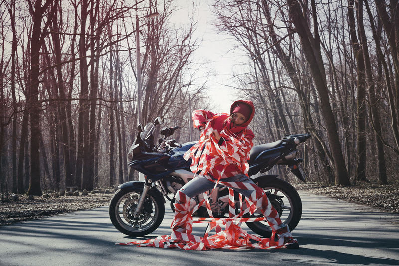 Full length portrait of young woman trapped in cordon tape by motorcycle on road in forest