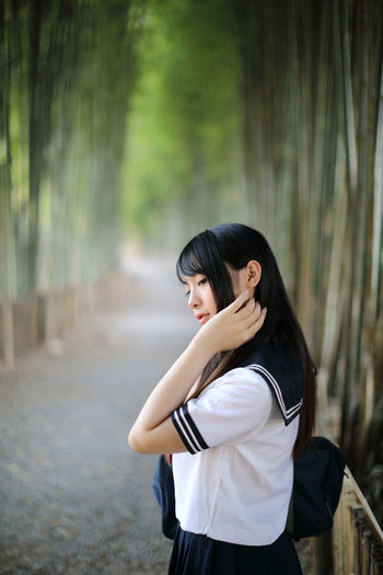 Side view of young woman in bamboo groove