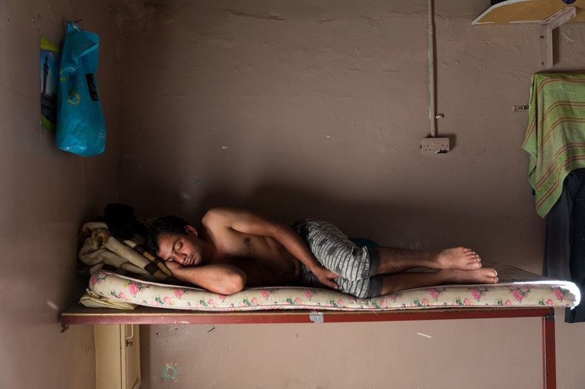 Raja 30 years old, from Rajasthan, India works as a car mechanic. Deep sleep minutes before getting up for his 12 hours daily work in a repair shop. Migrant Workers Kuwait The Human Condition
