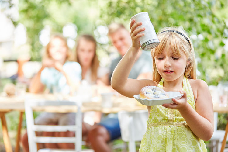 Smiling Girl Icing Doughnut While Family Sitting At Table Outdoors