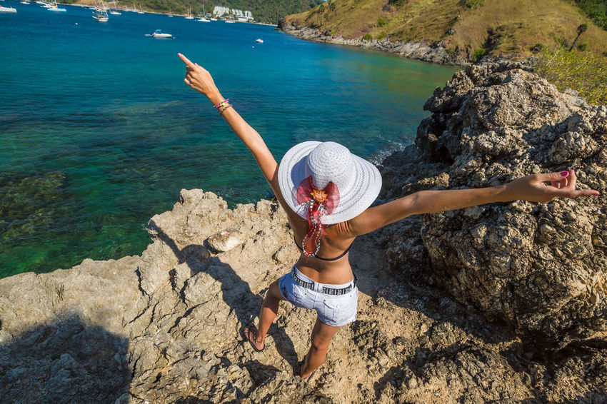 Back of happy and fashionable tourist woman with colorful sarong in turquoise water of Maya Bay famous lagoon of The Beach movie, Phi Phi Leh, Andaman Sea in Thailand Fashionable and happy tourist with sarong and pink wide-brimmed hat making a selfie on tropical famous beach of Nai Harn Beach, Rawai, Phuket, Thailand. Happy tourist enjoys panorama from Sail Rock View Point of kor 8 of Similan Islands National Park, Phang Nga, Thailand, one of the tourist attraction of the Andaman Sea. Happy woman with bikini and shorts, jumping in the air on Ya Nui Beach, a little cove divided by a rocky cape, Phuket, Thailand, Asia. Happy Koh Rok Islands Nui Beach Phang Nga Bay Phuket Thailand Tanning ☀ Thailand Vacations Woman Beach Beauty In Nature Casual Clothing Day Full Length Girl Koh Rok Leisure Activity Lifestyles Nature One Person Outdoors People Phang Nga Rawai Real People Rock - Object Scenics Sea Seascape Surin Islands Travel Destinations Tree Vacations Water Women Young Adult Young Women