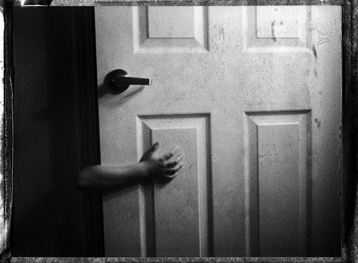 Close-up of hand with closed door