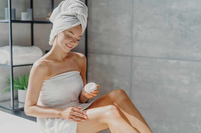 Smiling young woman wearing towel applying moisturizer at home