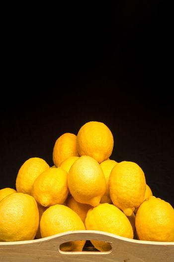 Stack of lemons in serving tray against black background