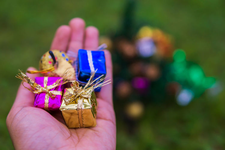 Close-up of hand holding gifts and decoration