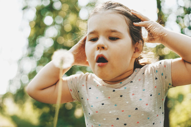 Close-up of cute girl blowing dandelion seed